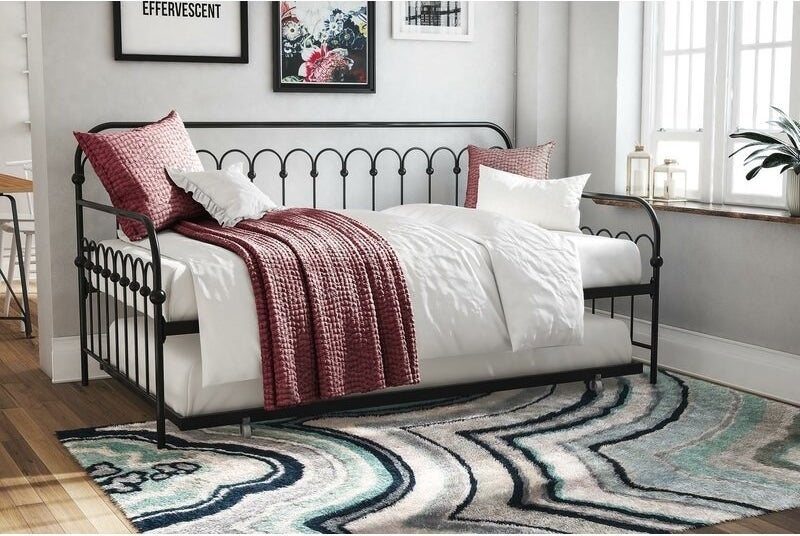 The steel trundle bed with rounded edges and side rails with two mattress on it.