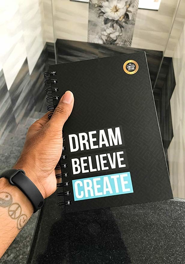 Black spiral bound notebook with the words 'Dream, Believe, Create' written on it.