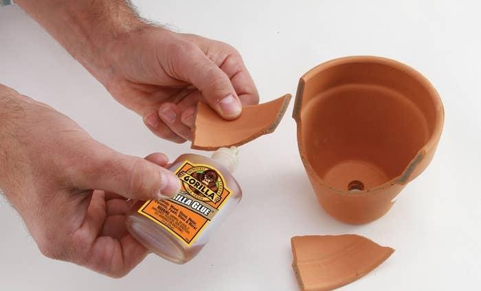 A person using Gorilla Glue to repair a flower pot
