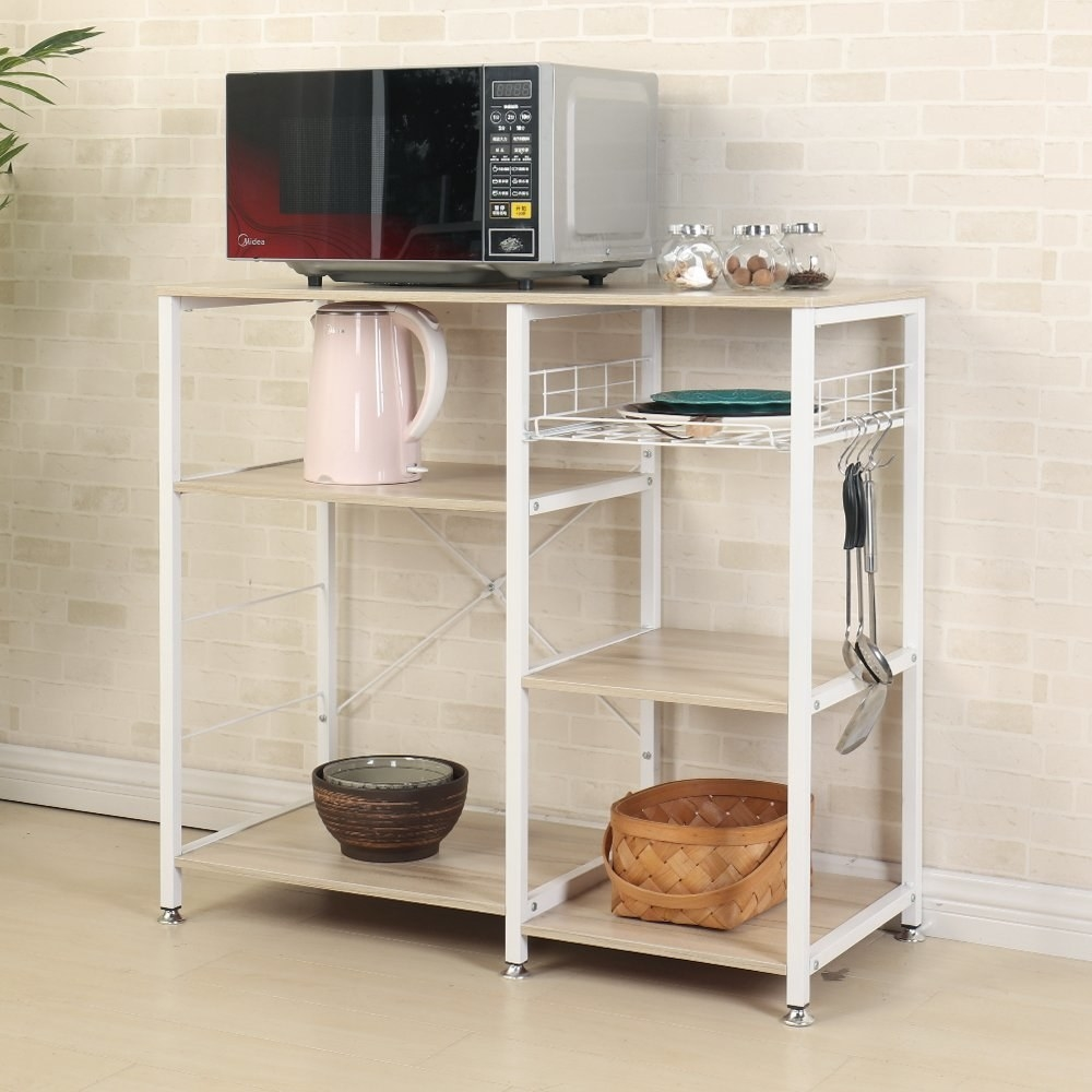A kitchen cart topped with mixing bowls, a microwave, and a tea kettle