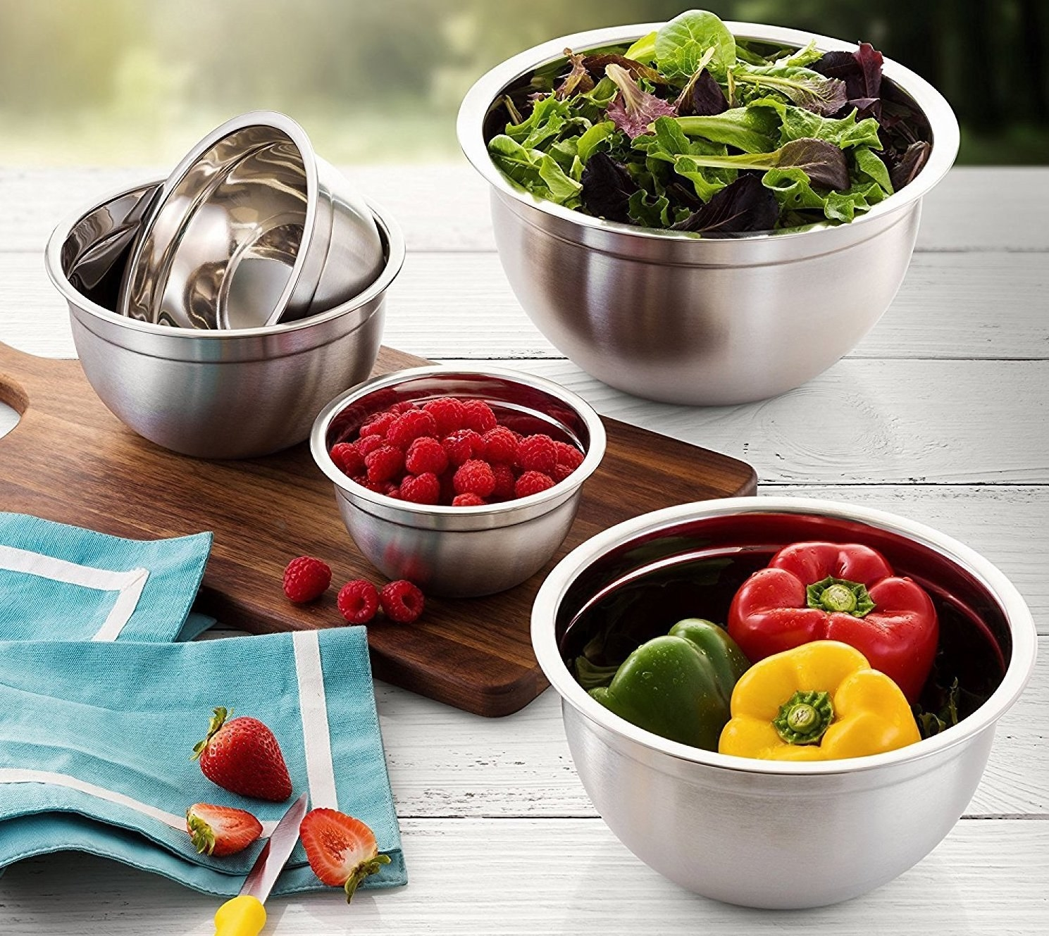 A set of stainless steel bowls filled with fresh fruits and veggies