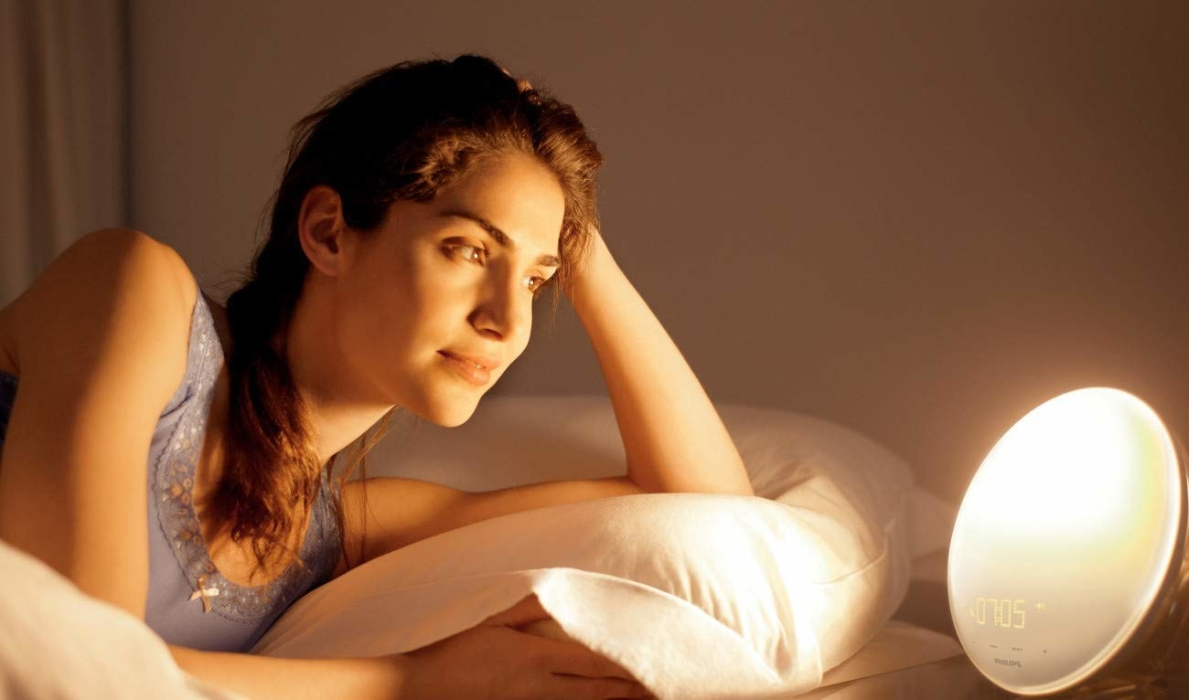 A person sitting up in bed and looking at a small around alarm clock on their bedside table the clock has a large round light