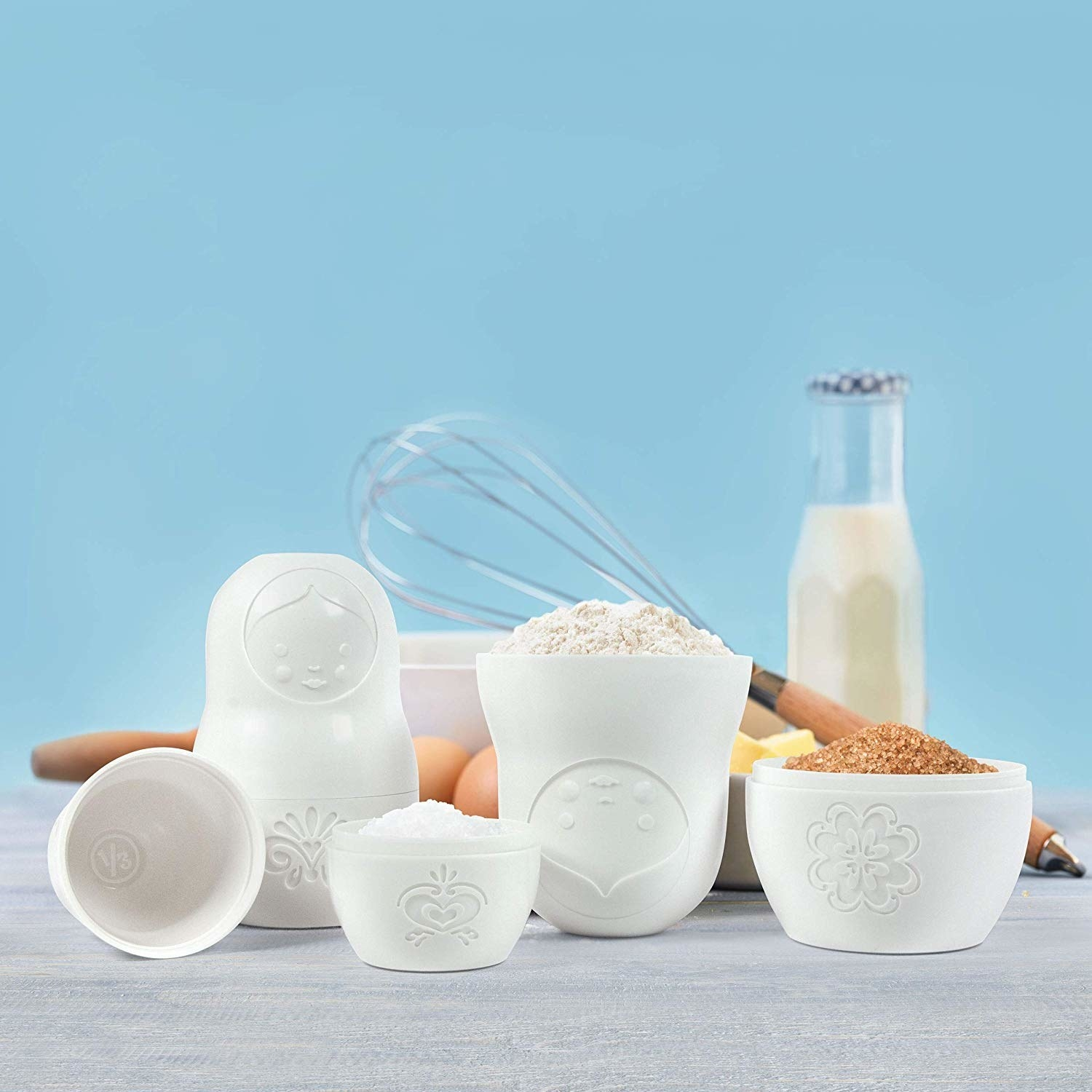 A set of nesting doll measuring cups filled with dry ingredients