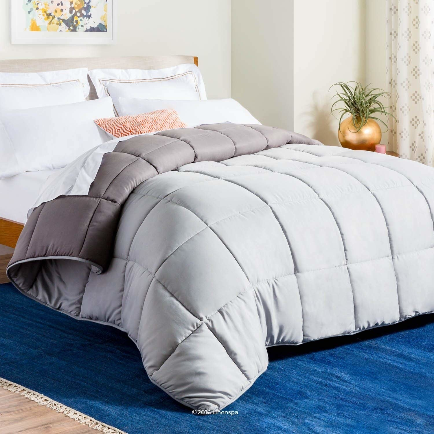 gray fluffy looking comforter on a bed
