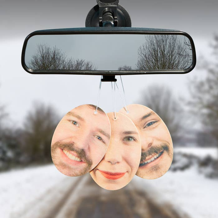 air freshener featuring someone's face hanging on car mirror