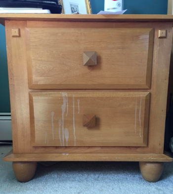 light wood nightstand with white liquid staining down the front
