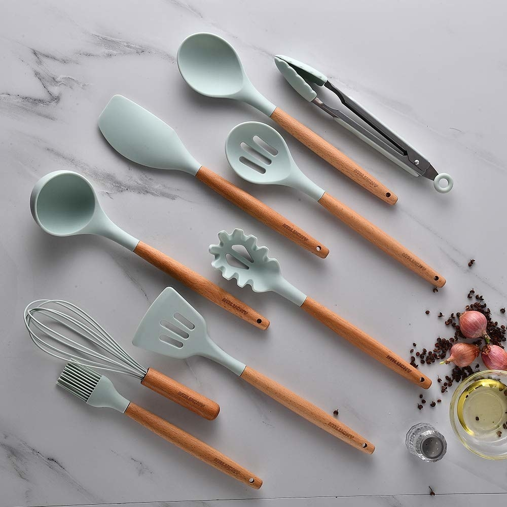 A set of nine kitchen tools lying flat on a plain background the top halves are silicone while the handles are made of wood