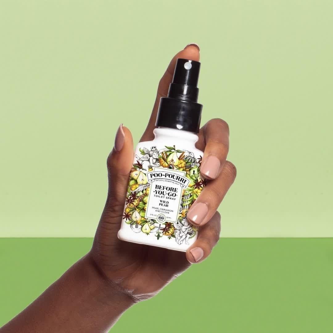 model's hand holding spray bottle of poo-pourri