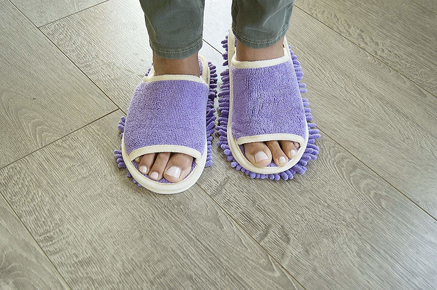 A person wear soft slippers There are short pieces of chenille yarn attached to the bottom