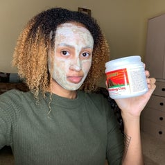 reviewer holding the mask's tub and wearing it on their face