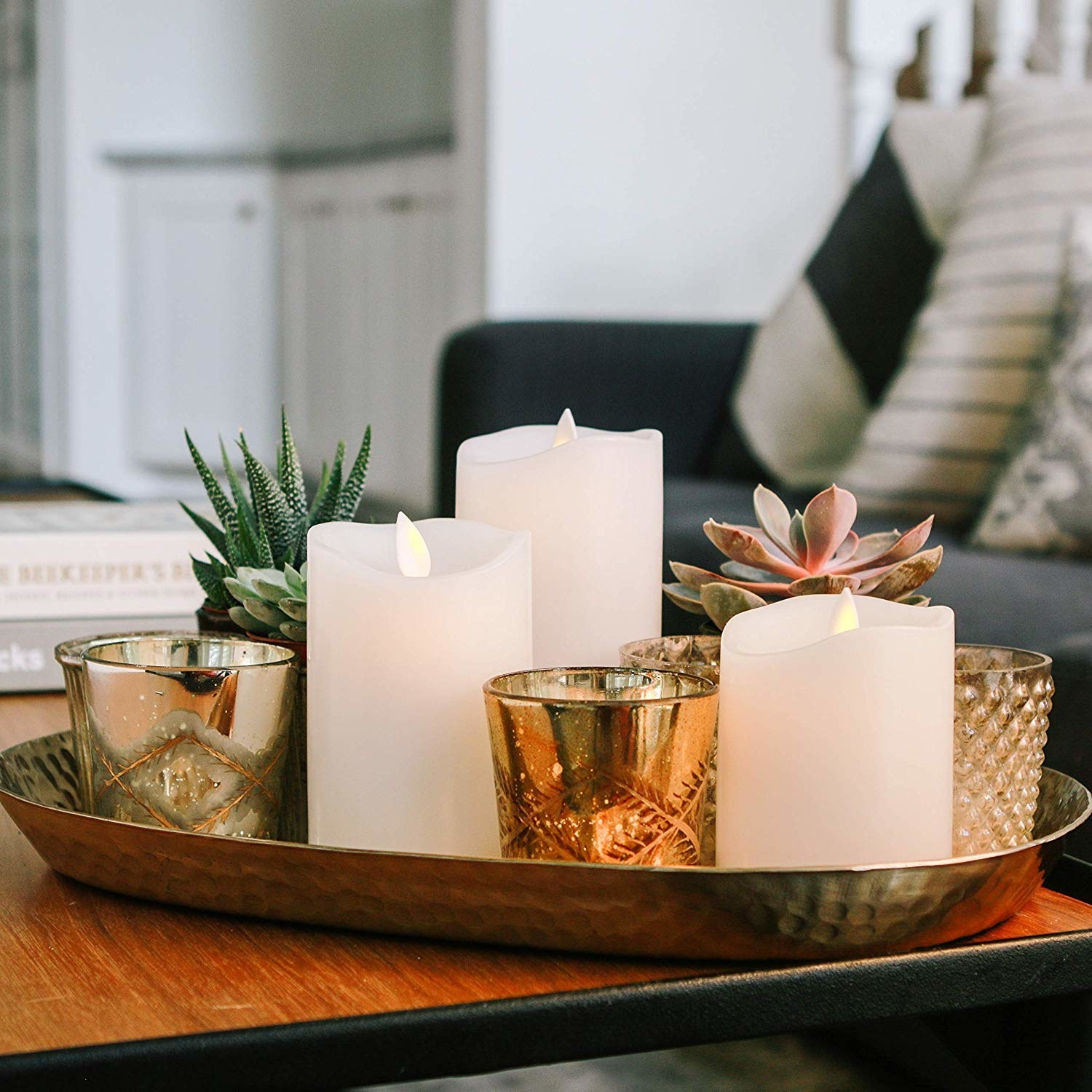three white candles of different sizes with a light flame in sitting in a tray