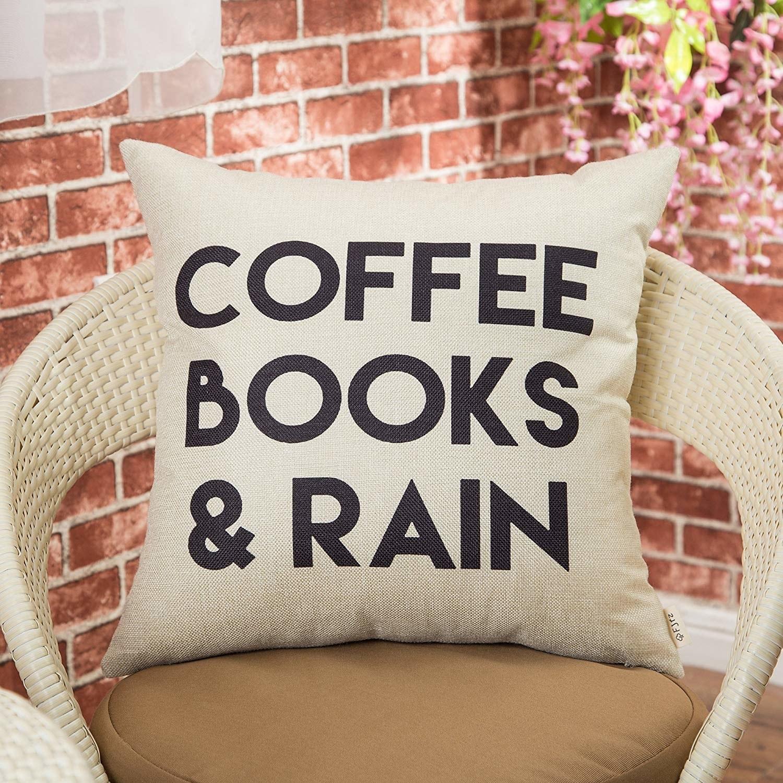 "white pillowcase with black text ""coffee books and rain"""