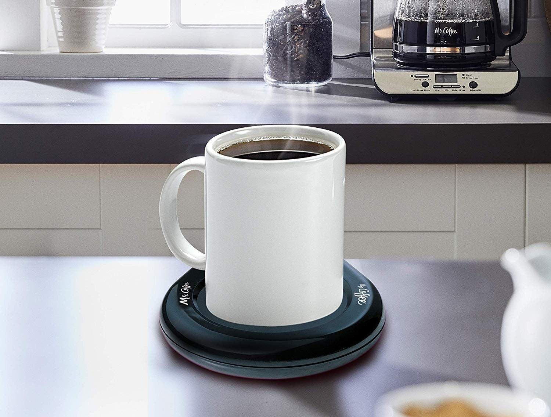 A small ceramic coffee mug sitting on an electrically heated coaster