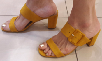 a model wearing the slip-on block heel sandals with a thick buckle in mustard yellow