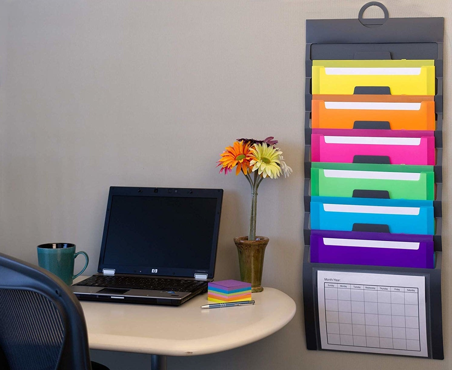 A vertical file folder hanging from the wall next to a table with a laptop