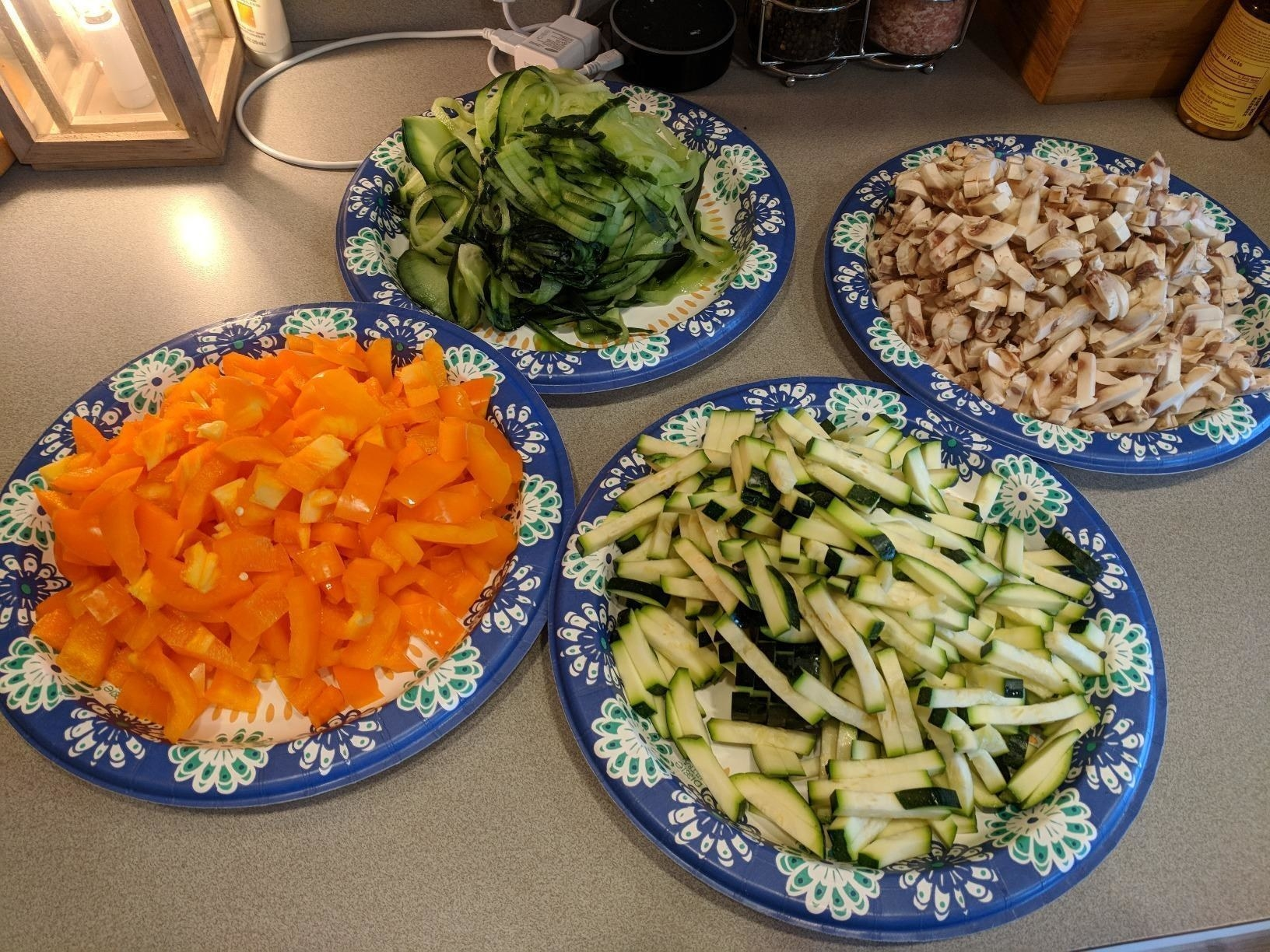Four plates full of veggies that have been chopped with the dicer