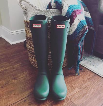 Green knee-high Hunter rain boots inside house