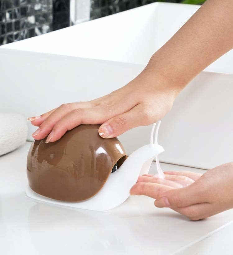 A hand pressing down on the shell of the brown and white snail dispenser, which is dispensing soap from the snail's mouth