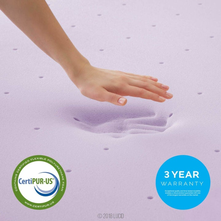 a model showing the imprint of their hand in the purple memory foam
