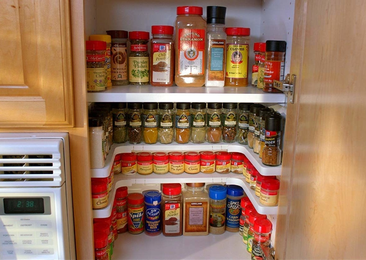 The U-shaped rack placed inside a cabinet with spices neatly organized on top of it