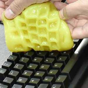 A person using gel cleaning putty to clean a computer keyboard