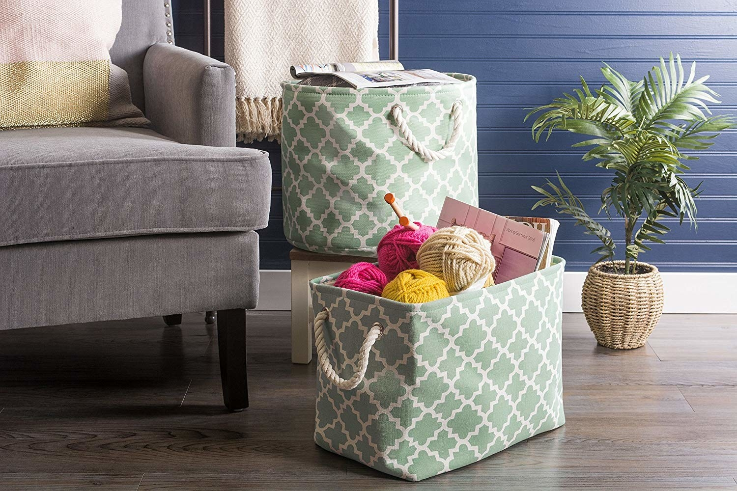 two bins in green and white lattice print, filled respectively with magazines and knitting