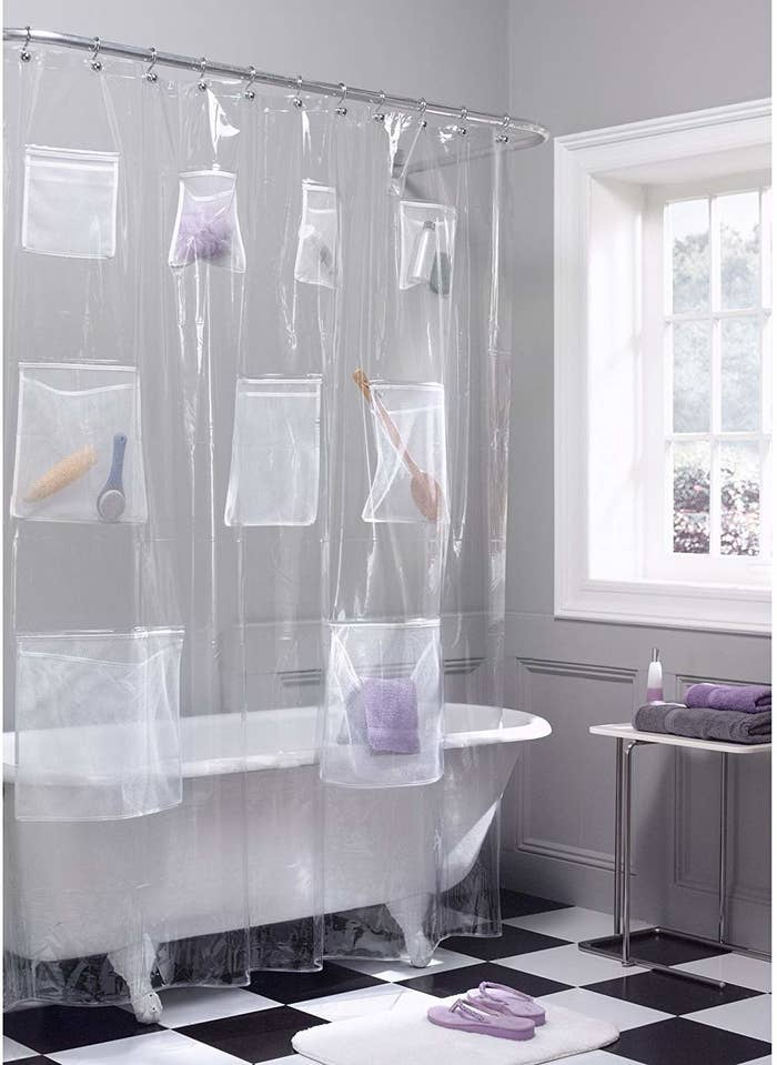The shower curtain hung over a free standing tub with the pockets filled with bathroom products