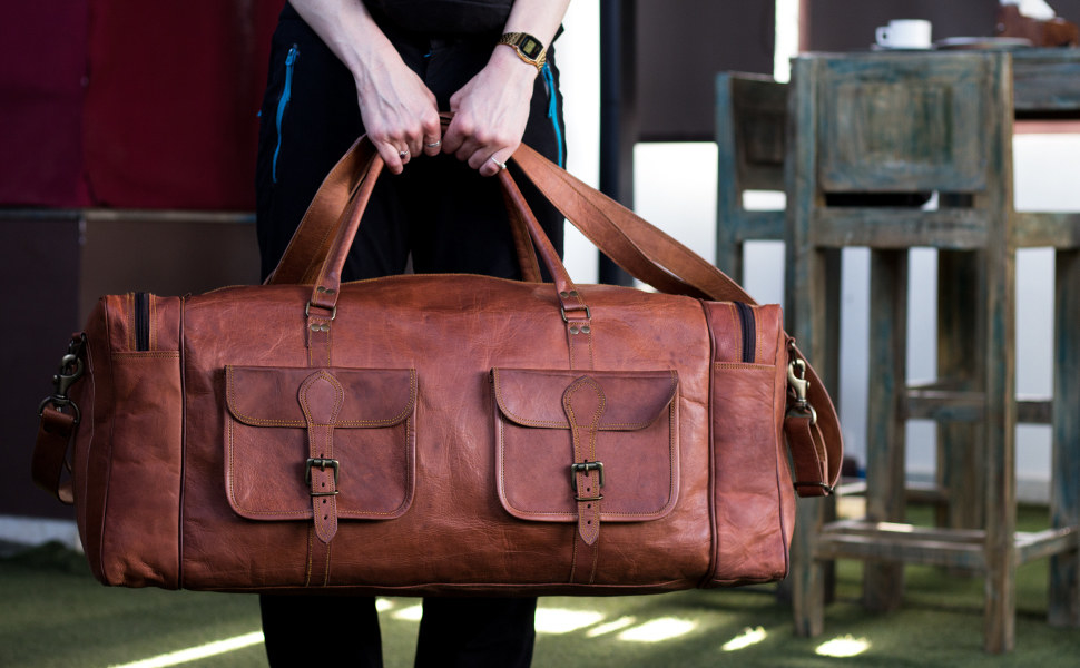 model holding a large leather duffel bag with two front pockets