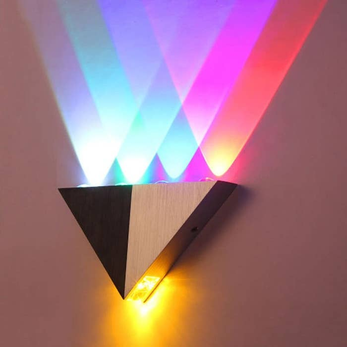 A black and white scone installed on a wall with different coloured lights being projected from it