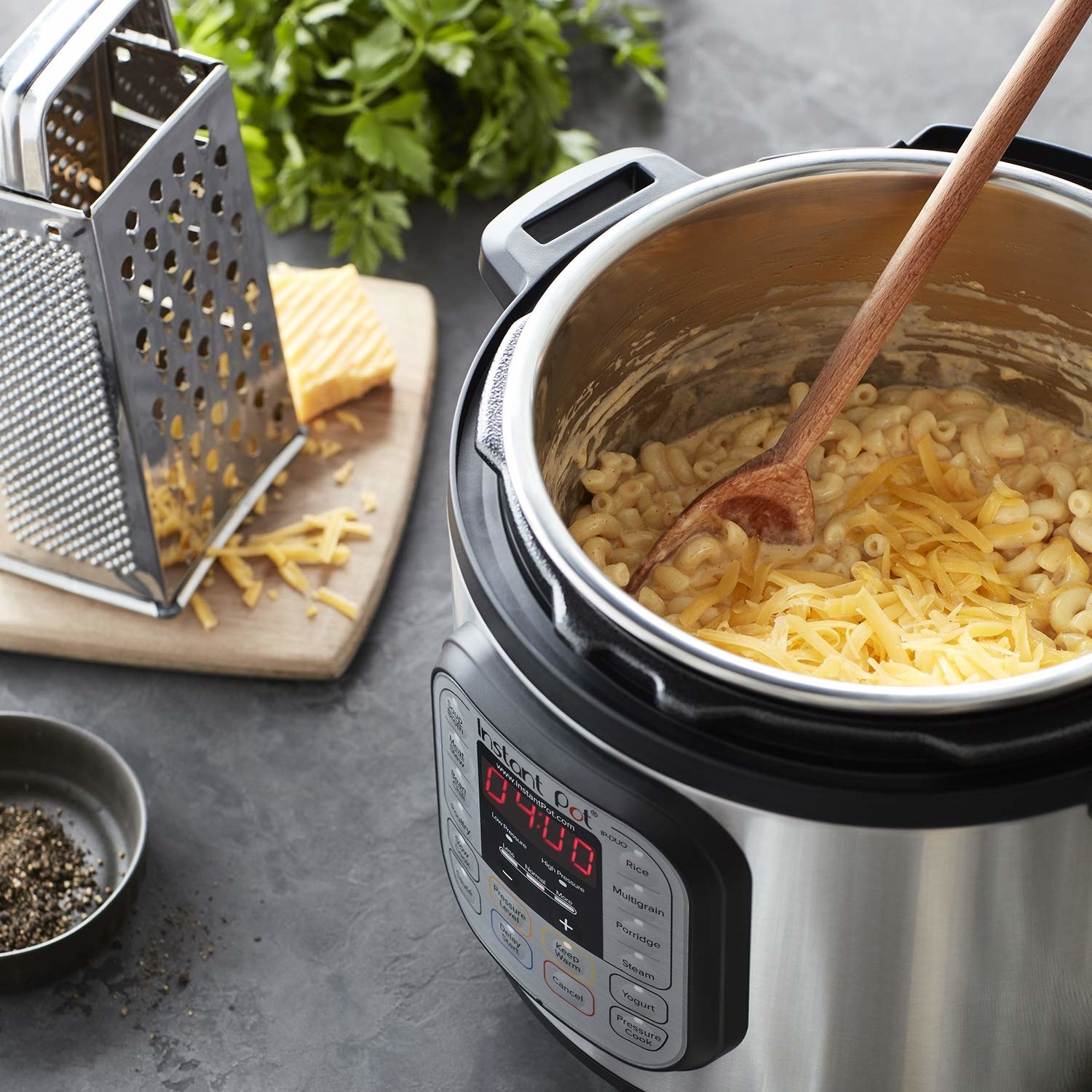 Instant Pot containing macaroni and cheese and shredder next to it