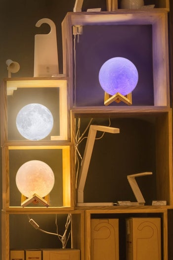three of the lamps illuminated different colors sitting on a shelving unit