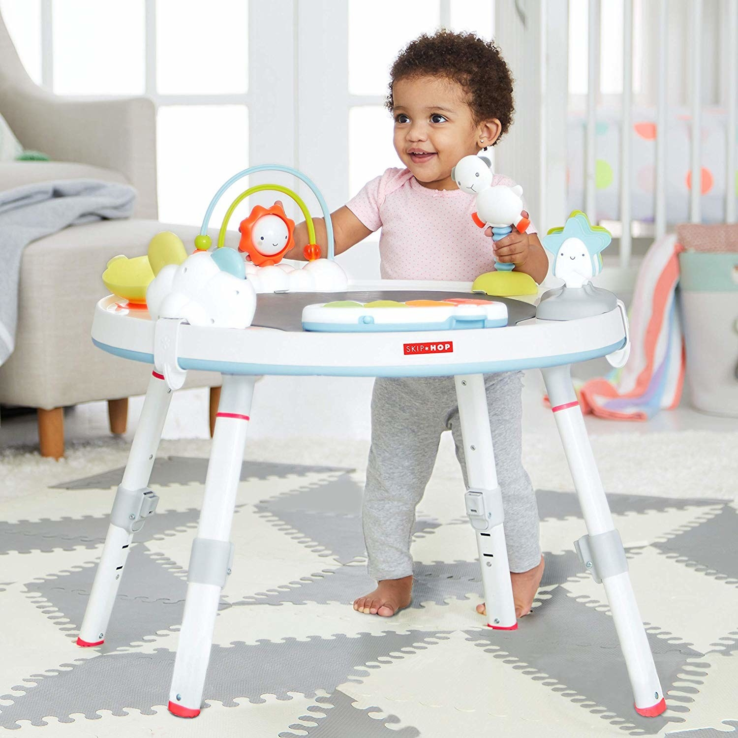 Child model standing next to white activity table with colorful toys attached