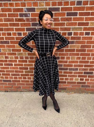 A reviewer wearing the black and white long-sleeve midi dress with white windowpane design