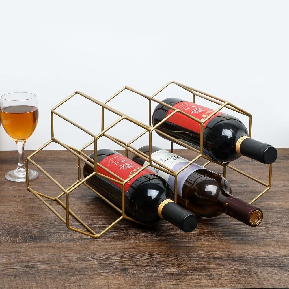 A geometric beehive shaped gold wine holder with room for seven bottles