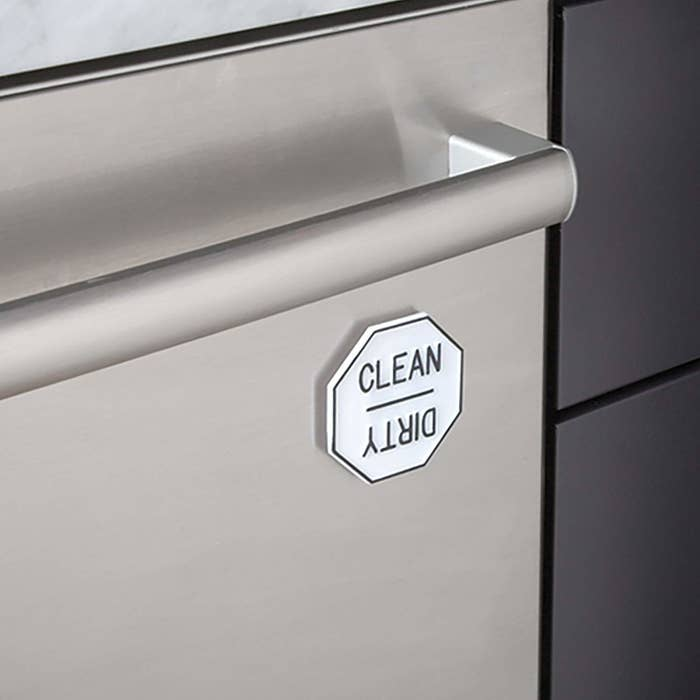 """The magnet on a dishwasher, which shows the word """"clean"""" on one side and the word """"dirty"""" when rotated"""