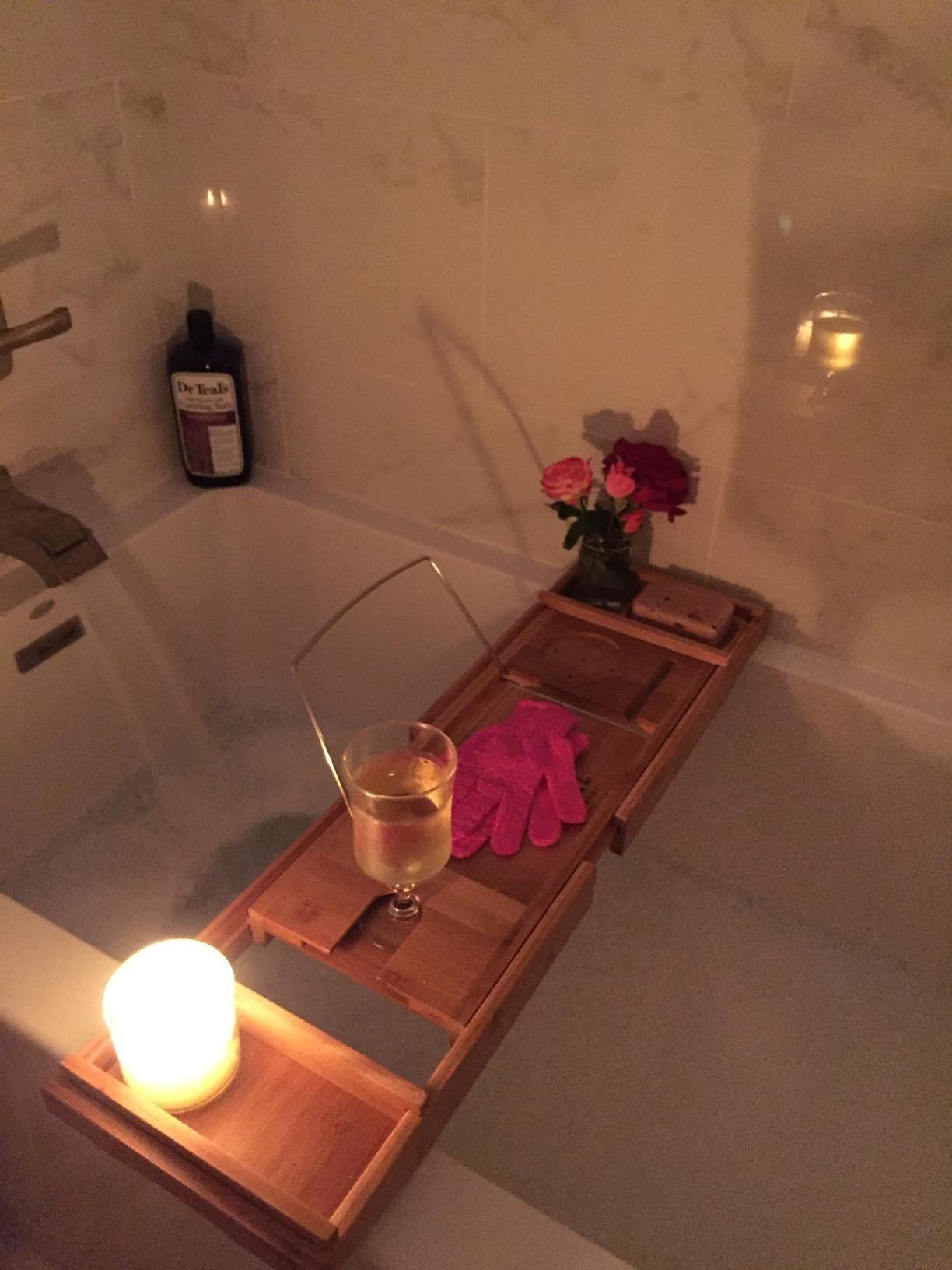 Reviewer image of a bath caddy with wine, candle, and flowers on it