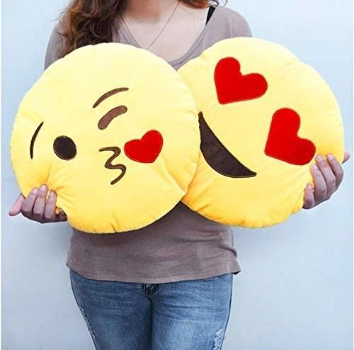 A heart-eyes and a kissing emoji cushions.