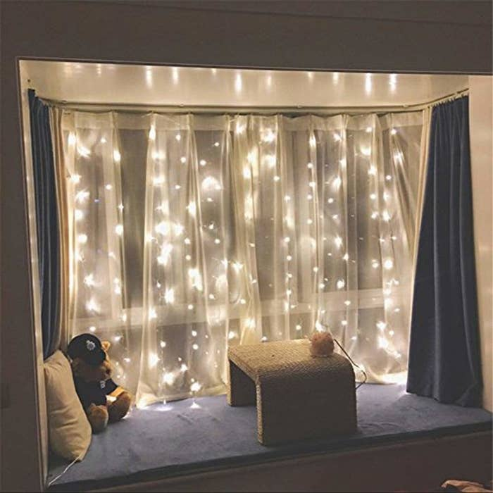 A dark window with sheer curtains and yellow fairy lights strung up illuminating it