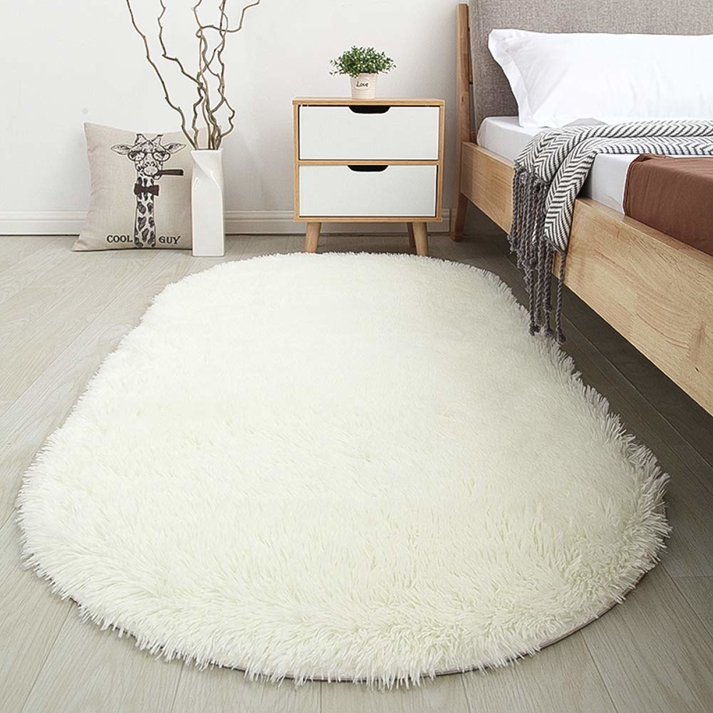 A white oval-shaped shaggy rug at the side of a bed