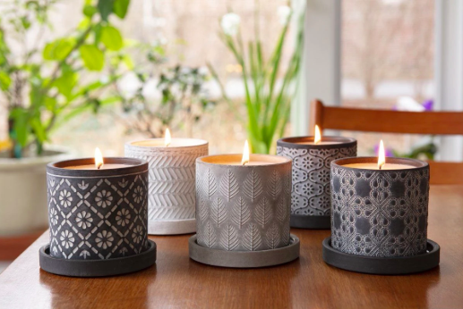 gray ceramic candle containers with various etched designs on them