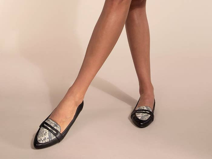 pointed-toe flats in black with snakeskin on top