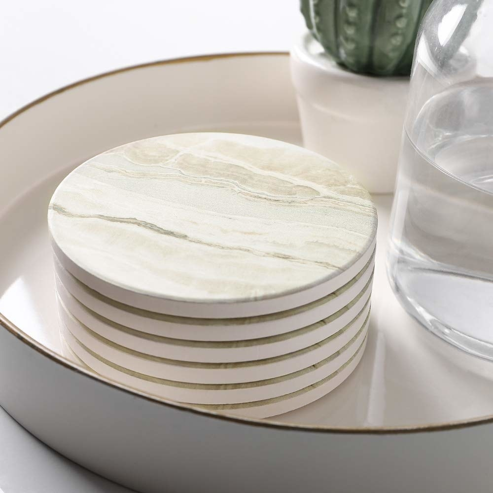 decorative tray with a stack of off-white marbled look round coasters