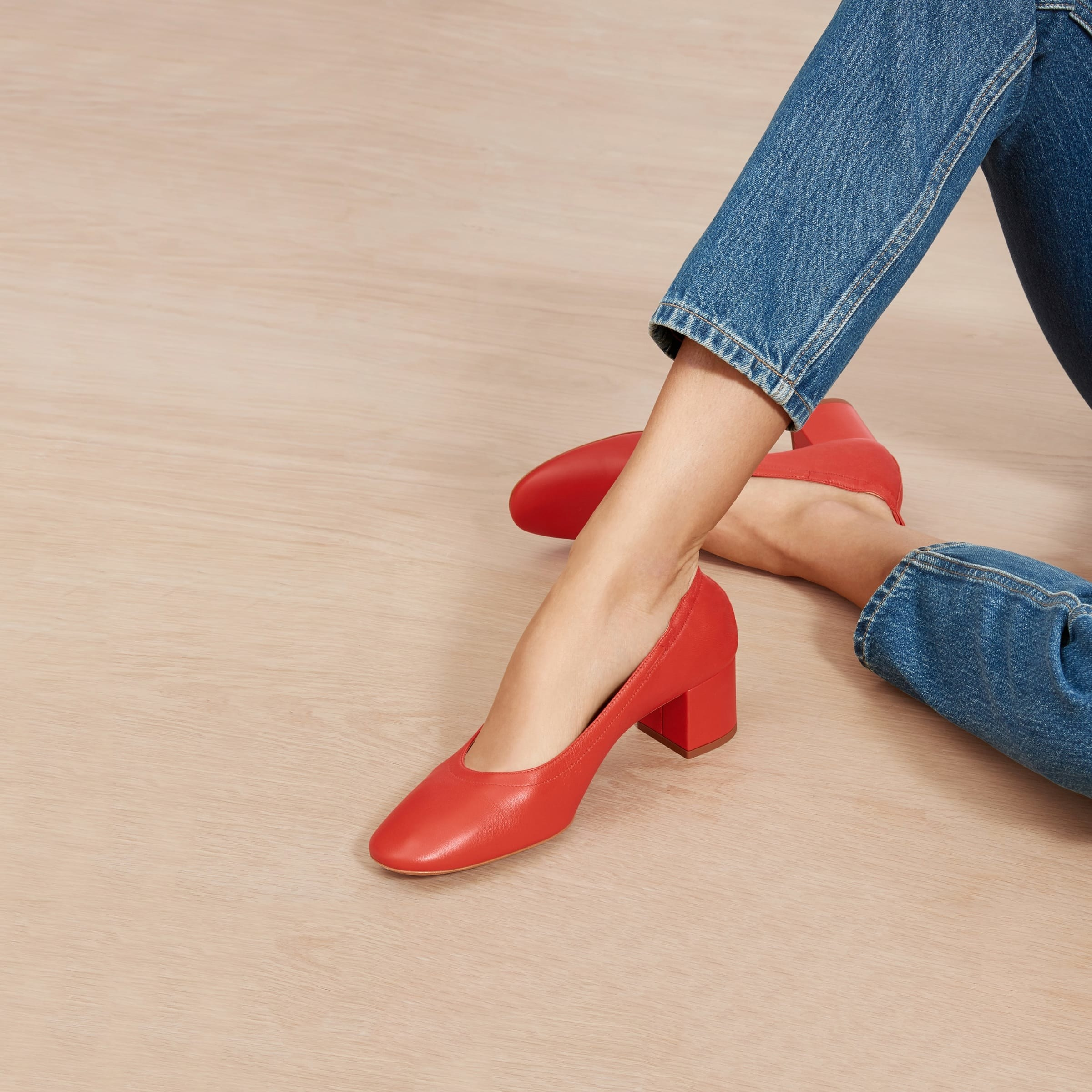 Model wearing the round toe shoe with a chunky short heel in red