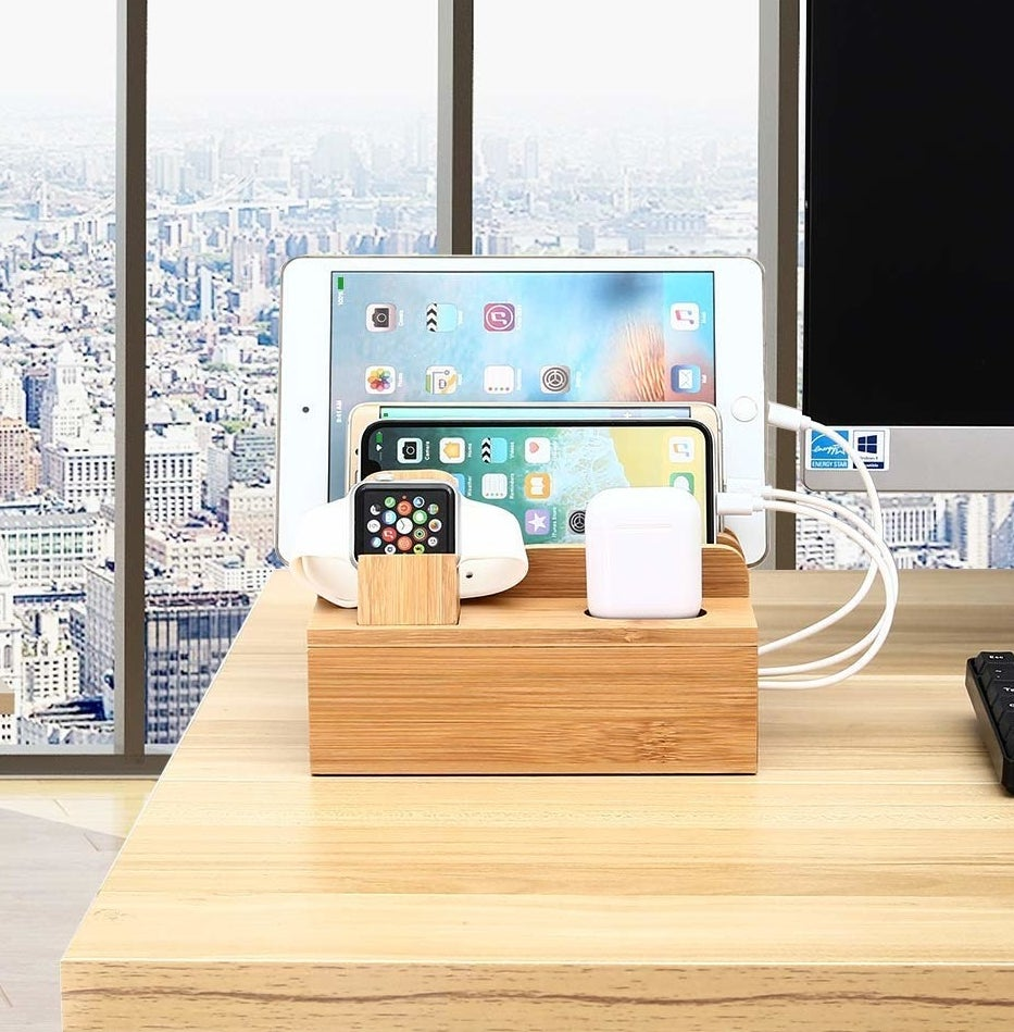 A bamboo station with slots for apple watch, airpods, phone, tablet