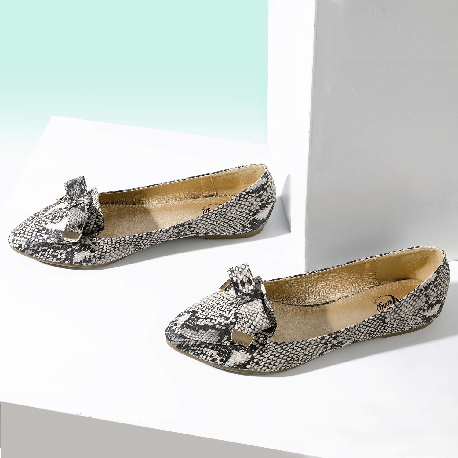 pointed toe flats with a bow on the top and black and white snakeskin print