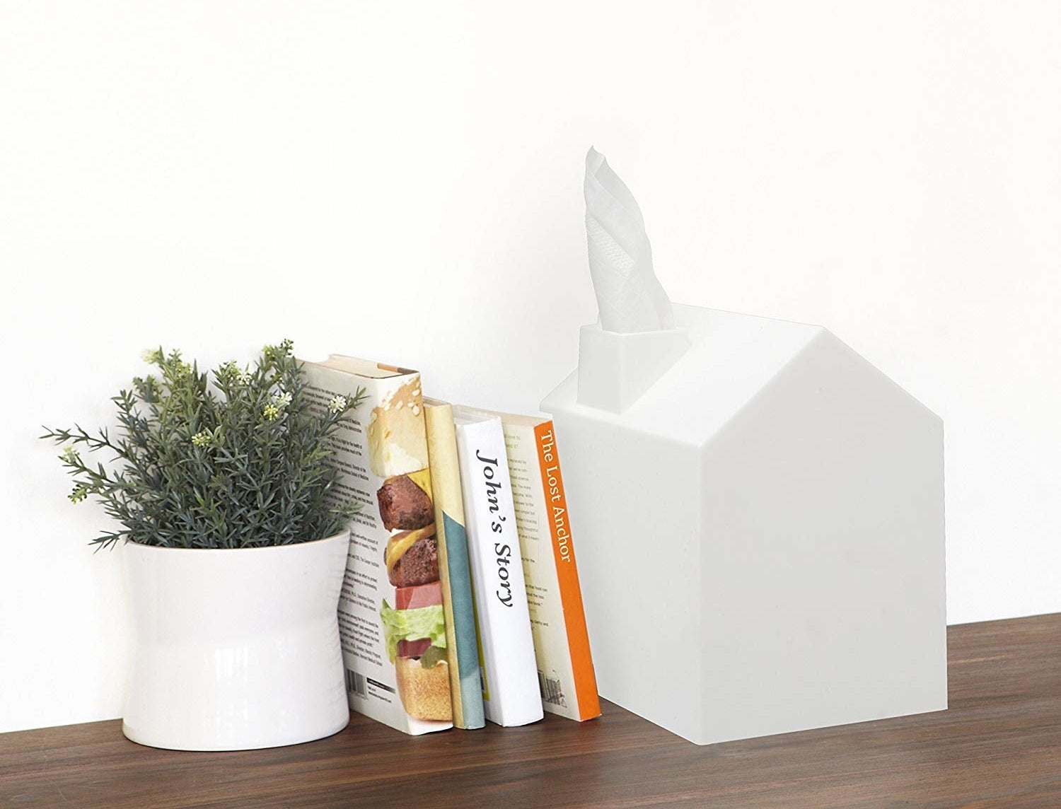 The tissue box cover next to some books and a plant