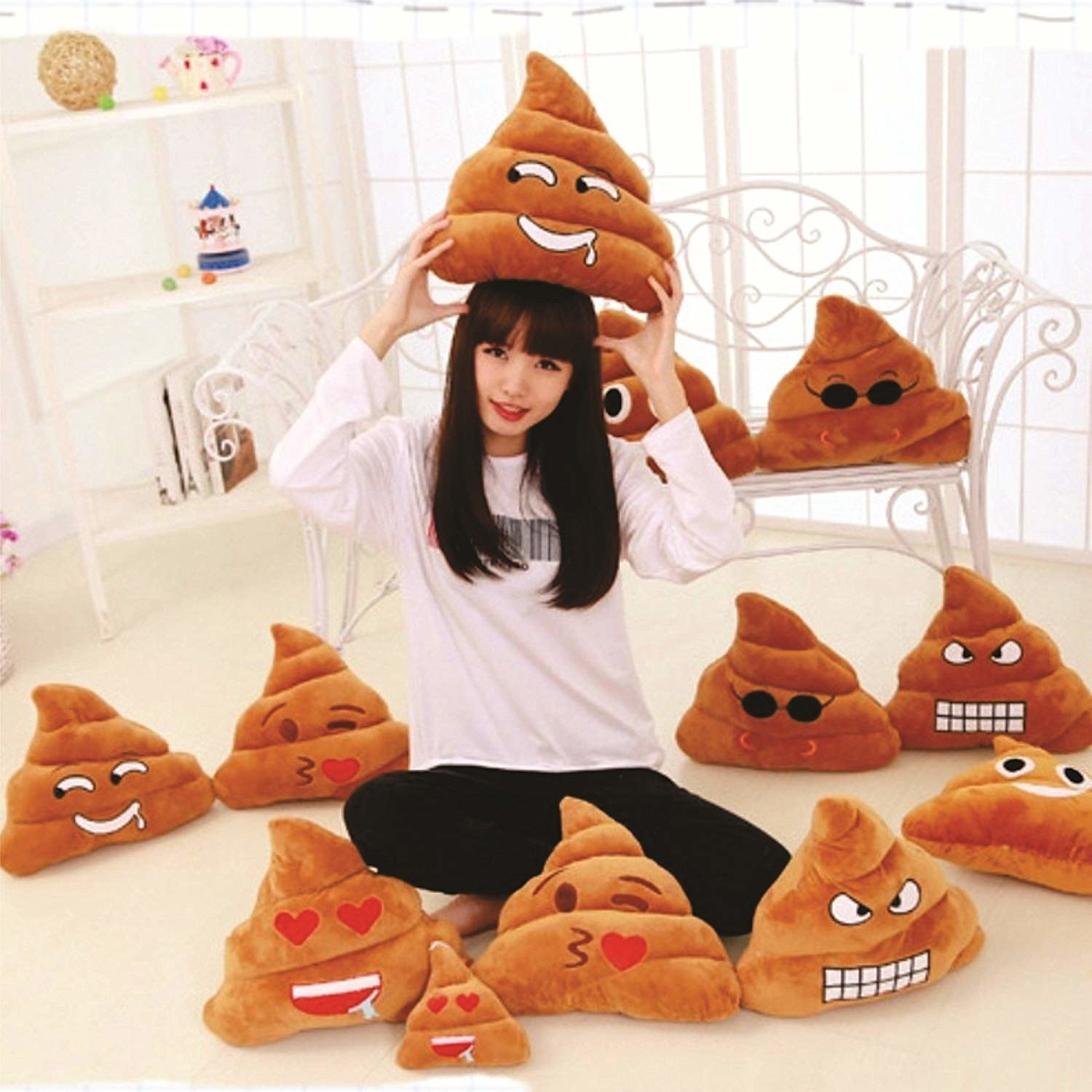 A person surrounded by poop-emoji cushions.