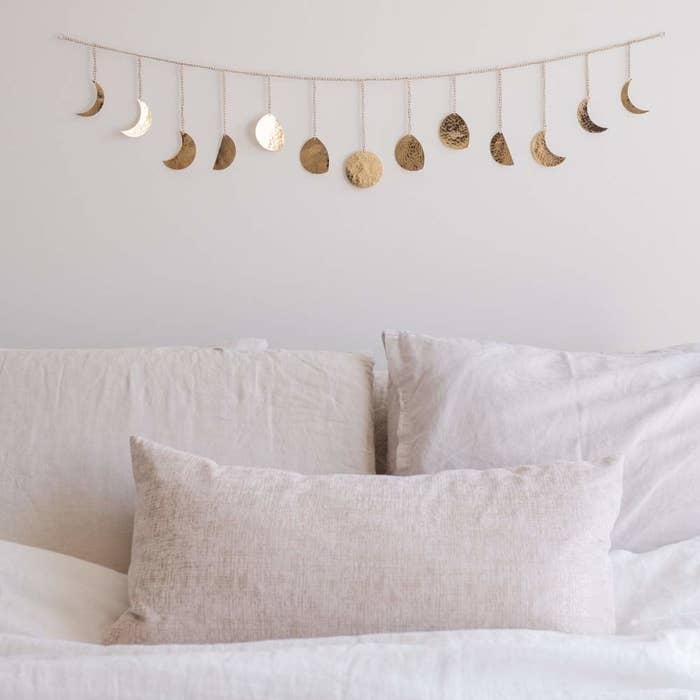 A gold garland strung above a bed with moons in waxing and waning phases strung along it