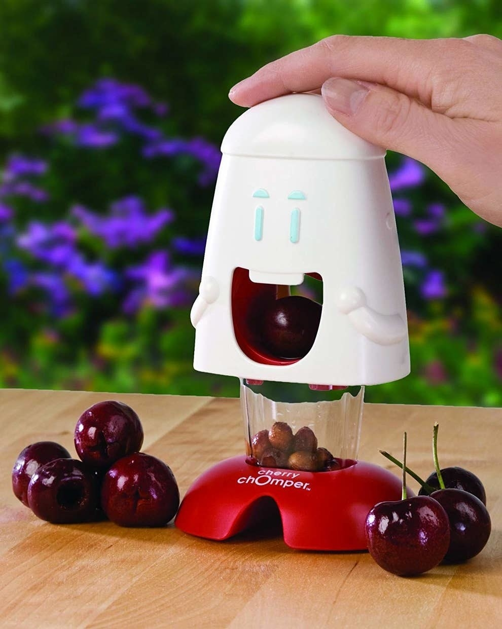white cartoon face with clear holder and base with a cherry in the mouth hole, showing how it removes the pits