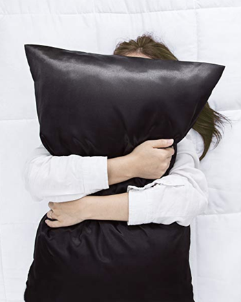 A model hugging a pillow with a black satin case
